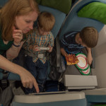 For the long flight, everyone had their own video monitor, which required some tutoring to learn how to use. Miranda demonstrates the wonders of the video screens to her wards.